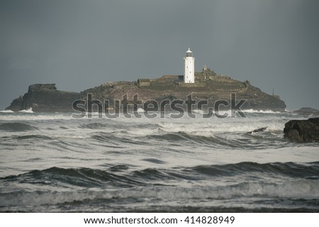 Godrevy lighthouse cornwall with rough sea and grey sky - stock photo