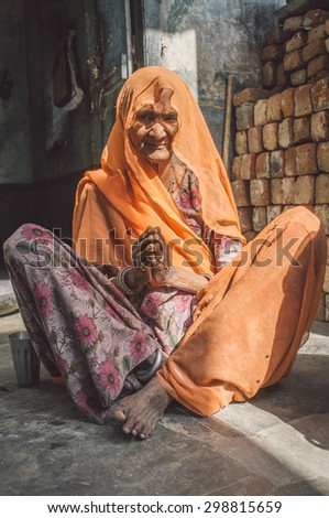 GODWAR REGION, INDIA - 13 FEBRUARY 2015: Elderly Indian woman in sari with covered head sits in doorway of home. Post-processed with grain, texture and colour effect. - stock photo