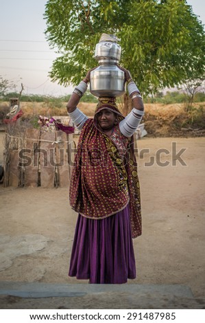 GODWAR REGION, INDIA - 12 FEBRUARY 2015: Tribeswoman decorated in traditional clothes, jewelry and upper arm bracelets holds water pots on head. Rabari or Rewari are an Indian community in Gujarat. - stock photo
