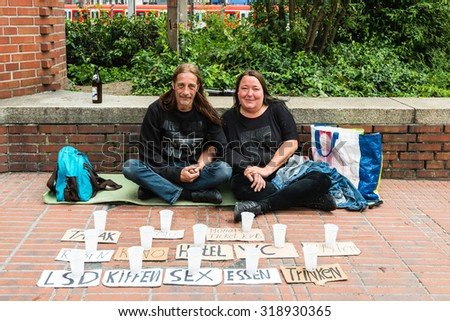 GOEPPINGEN, GERMANY - SEPTEMBER 12, 2015: A homeless couple is asking for support by placing a collection of cups with different options for donations like having a shower, going to the cinema, etc. - stock photo