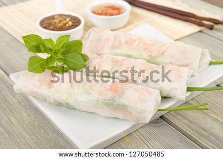 Goi Cuon - Vietnamese fresh summer rolls filled with prawns, herbs, rice vermicelli and vegetables. Served with hoisin and peanut sauce dip and nuoc mam cham. Wooden background. - stock photo