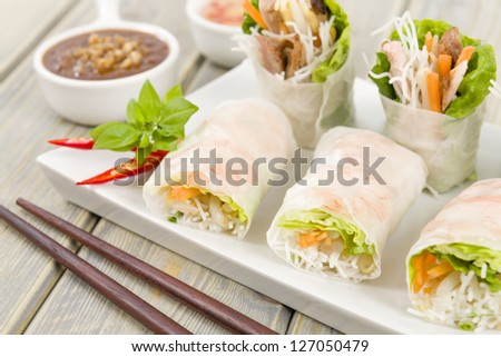 Goi Cuon - Vietnamese fresh summer rolls filled with prawns, pork, herbs, rice vermicelli and vegetables. Served with hoisin and peanut sauce dip and nuoc mam cham. Wooden background. - stock photo