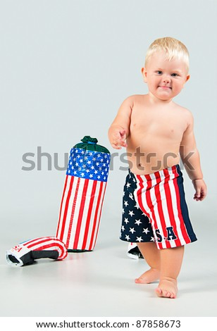 Going cute smiling baby in boxer shorts with  boxing gloves and pear - stock photo