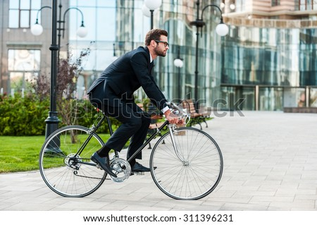 Going everywhere by his bike. Side view of young businessman looking forward while riding on his bicycle - stock photo