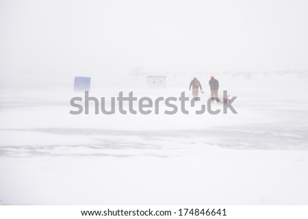 Going Ice FIshing in Snow Storm on Frozen Lake Erie - stock photo