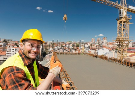 Going up - positive construction worker showing thumbs-up on high-rise city construction site - stock photo