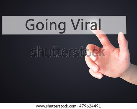 Going Viral - Hand pressing a button on blurred background concept . Business, technology, internet concept. Stock Photo