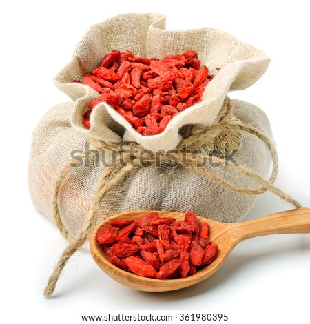 Goji berries in the sack bag with wooden spoon isolated on white