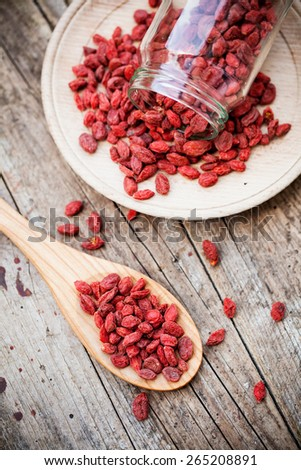 Goji berries on wooden plate - stock photo