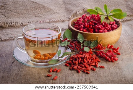 goji fresh antioxidant tea in glass cup and barberries in wooden desk - stock photo