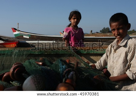 GOKARNA, INDIA - DECEMBER 14: The son of a fisherman from Indian state Karnataka, help prepares gear for fishing in the Indian ocean, December 14, 2008 in Gokarna, India. - stock photo