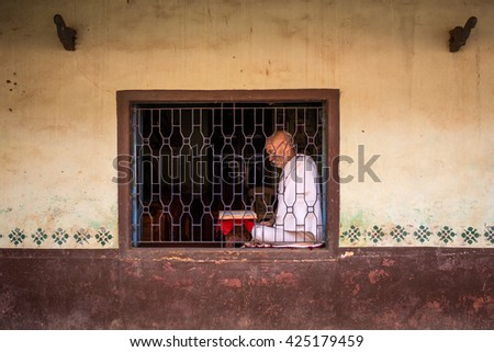 Gokarna, India - January 16, 2016: Unidentified temple brahmin in the temple window. The city is a holy pilgrimage site for Hinduists