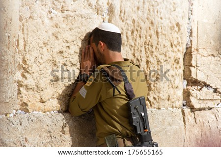 Golani Soldier praying at the Wailing Wall with weapon, Jerusalem, Israel - stock photo