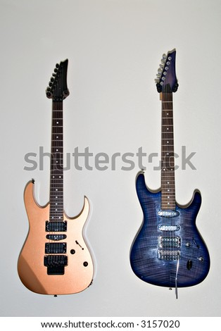 Gold and blue electric guitars hanging on wall