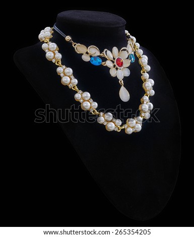 Gold and luxury pearl necklaces on black stand isolated in black background - stock photo