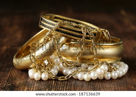 gold and pearl jewelry on vintage wooden background - stock photo