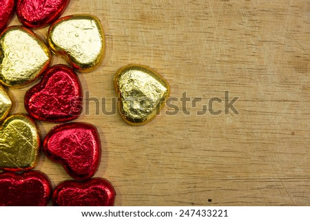 Gold and red hearts chocolate wrap foil on old wood background for valentine's day.  - stock photo