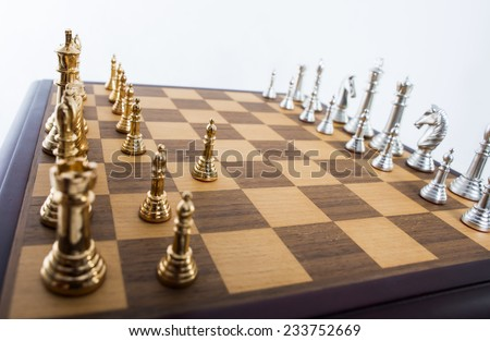Gold and silver chess pieces on a board. - stock photo