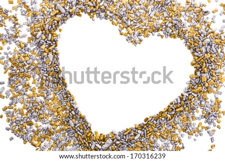 gold and silver grains of small size, scattered in disarray lined heart shape  isolated on white background  - stock photo