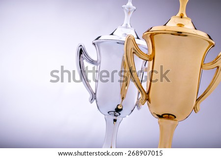 Gold and silver trophies waiting to be awarded to the winner and runner-up in a competition with focus to the gold cup in front - stock photo