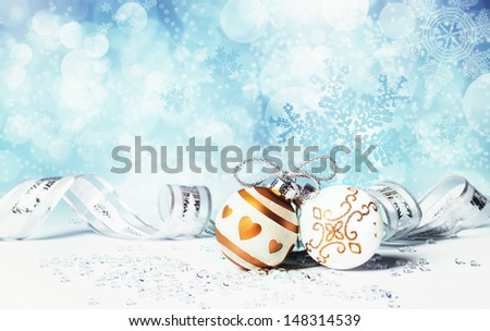 Gold and silver Xmas baubles on abstract winter background - stock photo
