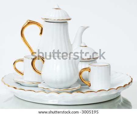 gold and white miniature tea set on white