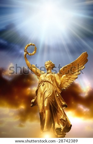 gold angel with rays of divine light over beautiful sky