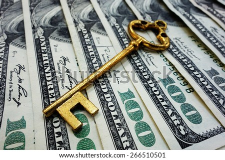 Gold antique key on hundred dollar bills