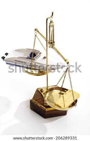 Gold bar and motor boat on scale - stock photo