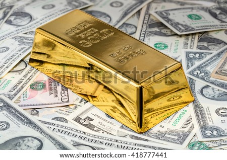 gold bar close-up on a background of dollar bills - stock photo