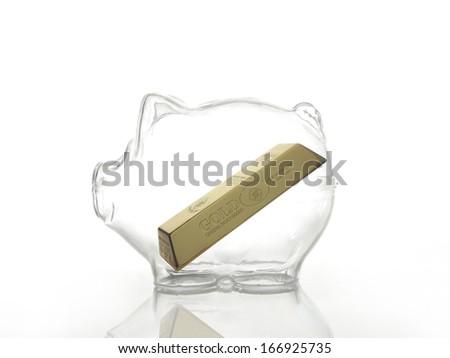 Gold bar inside glass piggybank shot on white background - stock photo