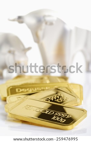Gold bars in front of bull and bear - stock photo