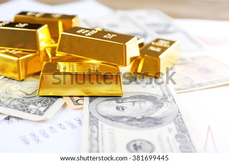 Gold bars on dollar banknotes, close up - stock photo