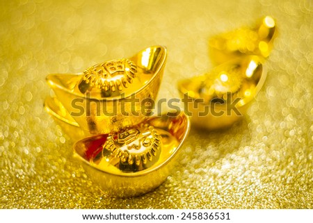 Gold bars on gold swirl background - stock photo