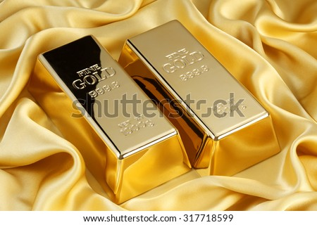 Gold bars on golden silk - stock photo
