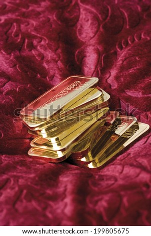Gold bars on red velvet - stock photo