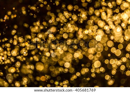 Gold bokeh of water and lights on black background