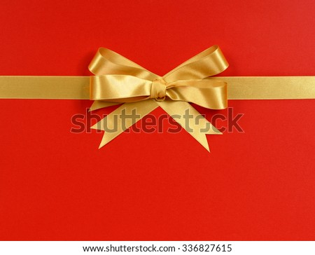 Gold bow gift ribbon horizontal isolated on red wrapping paper background - stock photo