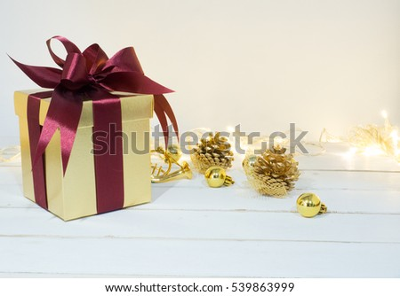Gold box with red ribbon and decoration golden object white background  on wooden table for Christmas and The New Year .