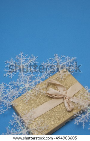 Gold box with wintry symbols.Snowflakes and Package/Christmas decoration and present on a blue background