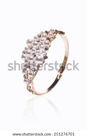 Gold bracelet inlaid with pearls on a white background - stock photo