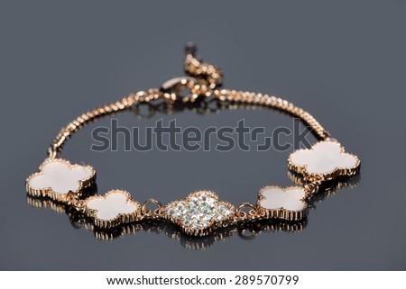gold bracelet on gray background.  - stock photo