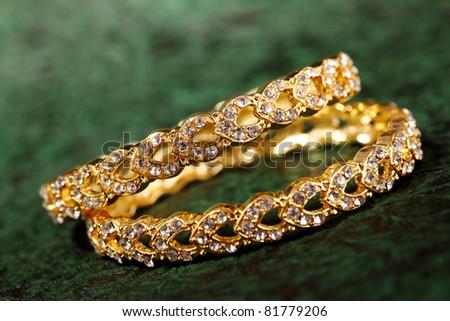 Gold bracelet on textured background. - stock photo
