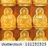 gold buddha on wall - stock photo
