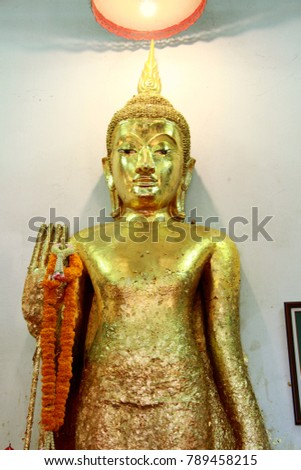 Gold buddha stand in temple thailand.