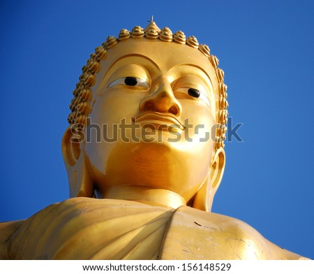 Gold buddha statue with blue sky - stock photo