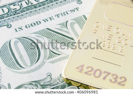 """Gold bullion and the inscription """"In God We Trust"""" on the US one dollar bill. A concept of the two most popular currency reserve in all countries in the world. - stock photo"""