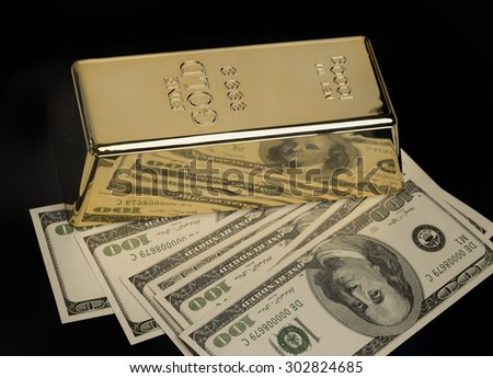 Gold bullion and US Dollar currency - stock photo
