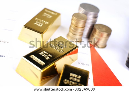 Gold bullion with coins on documents background - stock photo
