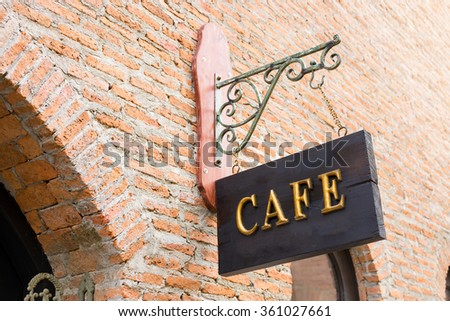 Gold cafe sign above a brick wall - stock photo